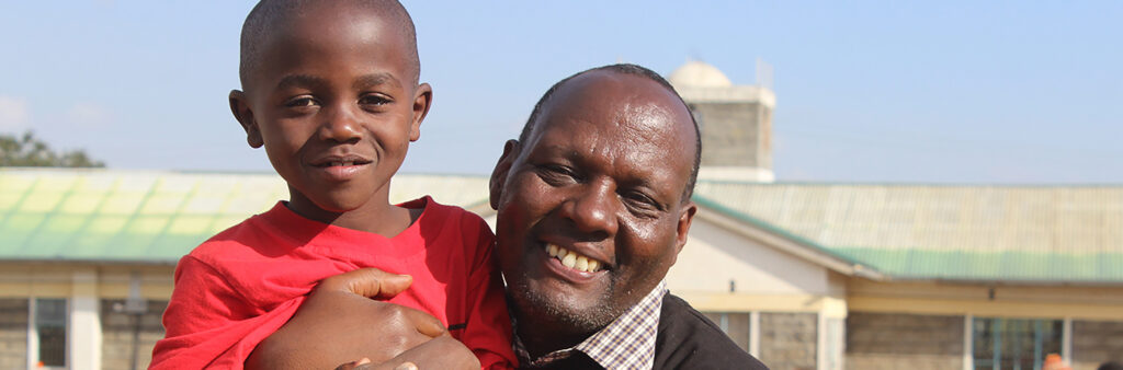 Kenianischer Mann hält kenianisches Kind in rotem T-Shirt