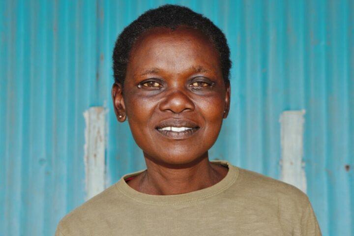 Kenianische Frau in beigem Pullover vor blauem Wellblech
