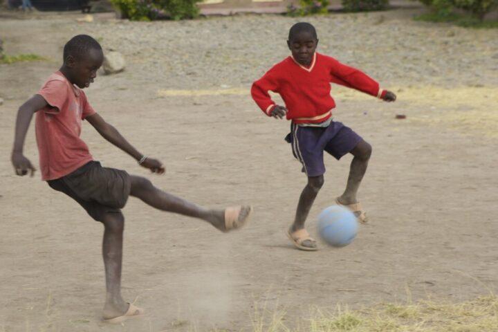 Zwei kenianische Jungen spielen Fussball