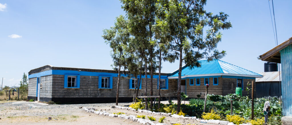 Längliches graues Steingebäude mit blauen Fenstern und blauem Dach, Bäume und Garten im Vordergrund