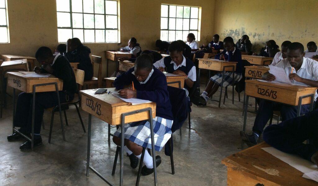 Klassenzimmer mit Einzelbänken und schreibenden Schülern