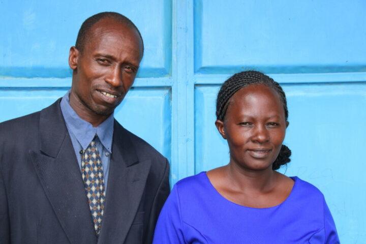 Kenianischer Mann in Anzug mit kenianischer Frau in blauem Kleid vor blauem Tor