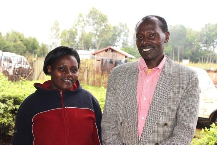 Kenianischer Mann in grauem Anzug und rosa Hemd mit kenianischer Frau in blau-roter Jacke