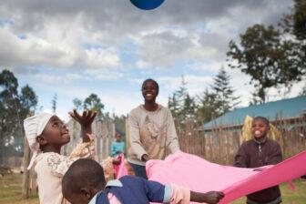 Fünf kenianische Kinder spannen ein pinkiges Tuch und spielen mit einem blauen Ball