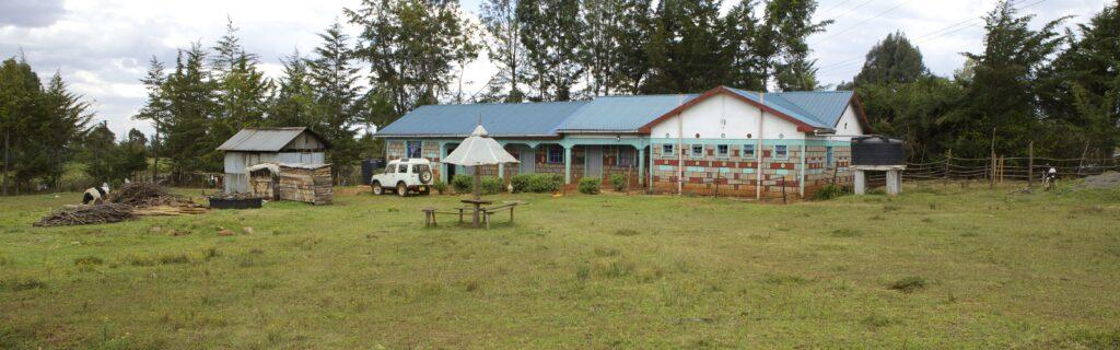Grosses Gebäude mit blauem Dach, davor eine kleine Wellblech-Hütte und ein weisser Jeep