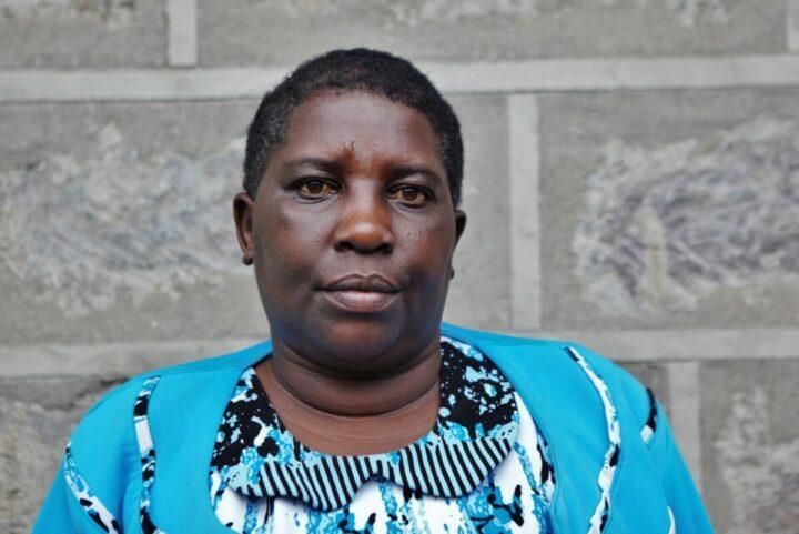 Kenianische Frau in blauem Kleid vor grauer Mauer