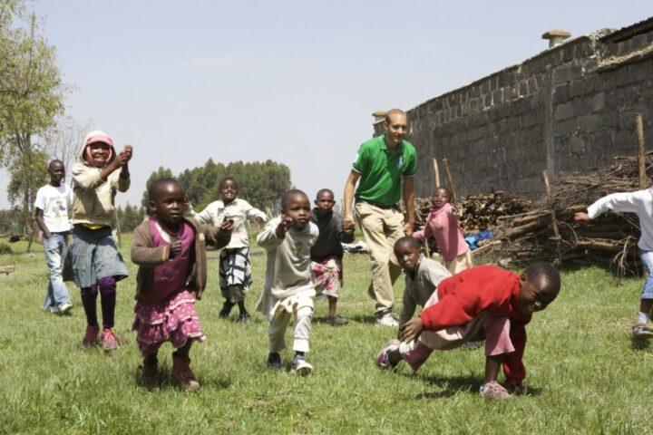 10 rennende kenianische Kinder, dazwischen ein Schweizer Volontär