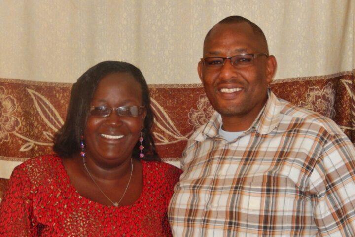 Kenianische Frau mit Brille und rotem Kleid Arm in Arm mit kenianischem Mann mit Brille und braun-weiss kariertem Hemd