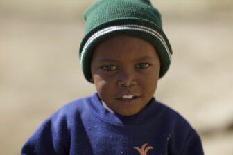 Kenianisches Kind mit grüner Mütze und blauem Pullover