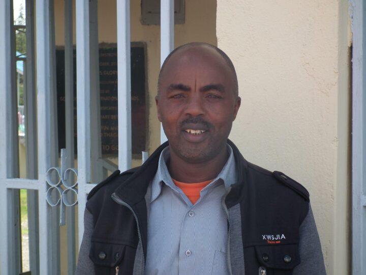 Kenianischer Mann mit grauem Hemd und schwarz-grauer Jacke