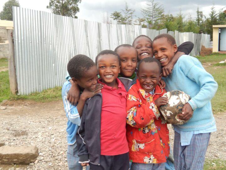 6 lachende kenianische Kinder, die sich umarmen und einen Fussball halten